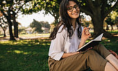 Woman writing in a book at park