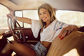 Beautiful woman traveling in a vintage car