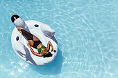 Woman relaxing on inflatable swan floating in pool