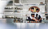 Chefs cooking food at commercial kitchen