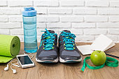 Fitness healthy concept,sneakers,apple,water and measuring tape on wooden background ,top view