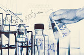 Researcher is dropping the reagent into test tube, with chemical equations background, in laboratory