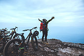 Asian women Travel photograph Nature. Travel relax ride a bike Wilderness in the wild. Standing on a rocky cliff. Thailand