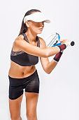 Professional Female Tennis Player with Racket Serving Ball. Studio Shot.