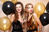 Beautiful young girls in elegant evening dresses with festive balloons. Beauty face.