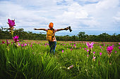 Asian woman travel nature. Travel relax. Photography Cucumber sessilis flower field.