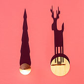 Wooden toy Christmas tree and toy deer with long shadow on red surface