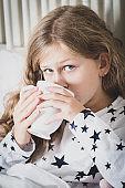 Sick child drinking tea