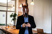 Business man with Horse Mask Using Mobile at Office