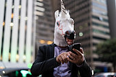 Business man with Unicorn Mask using mobile at city