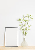 Picture frame and spring tree branches in a vase