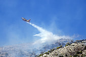 Firefighting plane extinguishes a fire on the hillside . Greece.