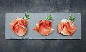 Italian prosciutto crudo or spanish jamon. Raw ham on stone cutting board