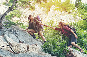 Group Hiker woman helping her friend climb up the last section of sunset in mountains. Traveler teamwork walking in outdoor lifestyle adventure and camping. Travel Concept.