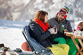 Skiers couple drinking and talking in cafe on skiing