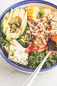 Vegan healthy rainbow salad, buddha bowl with quinoa, tofu, avocado and kale.