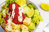 Vegan buddha bowl with beetroot meatballs, vegetables, tahini dressing and baked tofu, macro. Healthy vegan food concept.