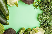 Assortment of green vegetables on green background, food frame.