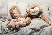Baby girl sleep in bed, toddler dream. Child with teddy bear. Comfort home relax