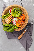 Vegan buddha bowl with tofu, spinach, avocado, rice and vegetables. Healthy vegan food concept.