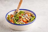 Bright vegan salad with arugula, sweet potato, radish, tahini dressing and cucumber, white background, copy space. Healthy vegan food concept.