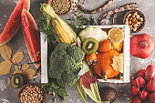 Autumn harvest in a wooden box. Fruits, vegetables and cereals, healthy food background.