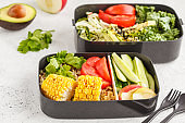 Healthy meal prep containers with quinoa, avocado, corn, zucchini noodles and kale. Takeaway food.
