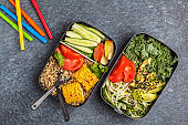 Healthy meal prep containers with quinoa, avocado, corn, zucchini noodles and kale. Takeaway school food. Dark background, top view.