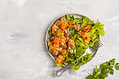 Healthy quinoa salad with roasted pumpkin and greens, top view, copy space. Healthy vegan food concept.