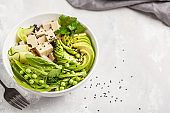 Green buddha bowl with tofu, rice, avocado and vegetables. Healthy vegan food concept.