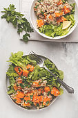 Healthy quinoa salad with roasted pumpkin and greens, top view. Healthy vegan food concept.