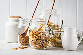 Raw breakfast cereals: granola, muesli, oatmeal in jars, white background.