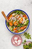 Bright vegan salad with arugula, sweet potato, radish, tahini dressing and cucumber, white background, top view. Healthy vegan food concept.