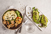 Cauliflower steak with grilled champignons and hummus and avocado toast, top view.