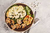 Cauliflower steak with grilled champignons and hummus, top view.