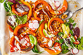 Baked pumpkin with chickpeas on a baking sheet with avocado, tahini and vegetables.