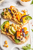 Vegan healthy sandwiches with hummus, chickpeas, baked vegetables and basil on white board.