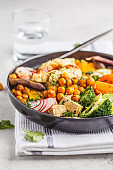 Vegan Buddha bowl with baked vegetables, chickpeas, hummus and tofu.
