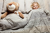 Kid girl sleep on pillow with teddy bear, bedtime. Comfort night rest