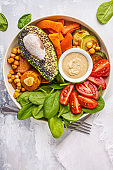 Vegan salad bowl with baked vegetables, chickpeas, avocado and tahini dressing on a white background, top view.