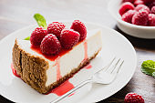 Cheesecake with raspberries and berry sauce on white plate