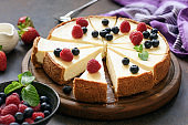 Classic plain New York Cheesecake sliced on wooden board