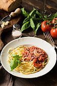 Spaghetti with tomato sauce, grated parmesan cheese and shrimps on rustic wood table