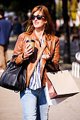 Fashionable, nice and attractive young woman is shopping in the city with paper bags in her hand.