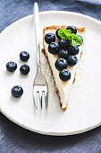 Cheesecake with fresh blueberries on white plate, selective focus