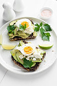 Rye bread toast with avocado, egg, white cheese
