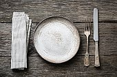 Table setting with vintage silverware, empty plate and napkin