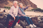 Senior people together in love - Elderly couple sitting on the beach hugging and looking and pointing with arm outstretched towards the horizon at sunset. Concept of vacation, leisure time, relaxation