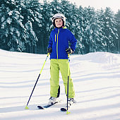 Professional skier teenager boy in sportswear on skis in winter forest at mountain