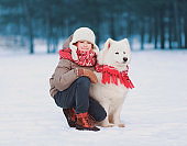 Portrait happy child boy sitting with white Samoyed dog in winter day on snow in park